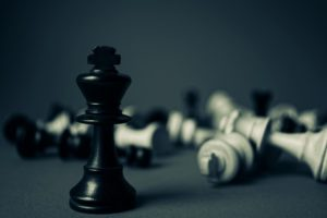 Chess pieces with black piece standing