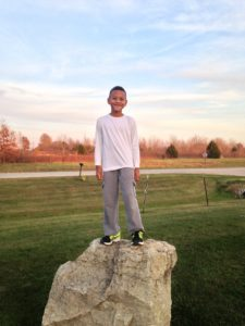 young boy on rock under beautiful dusk sky